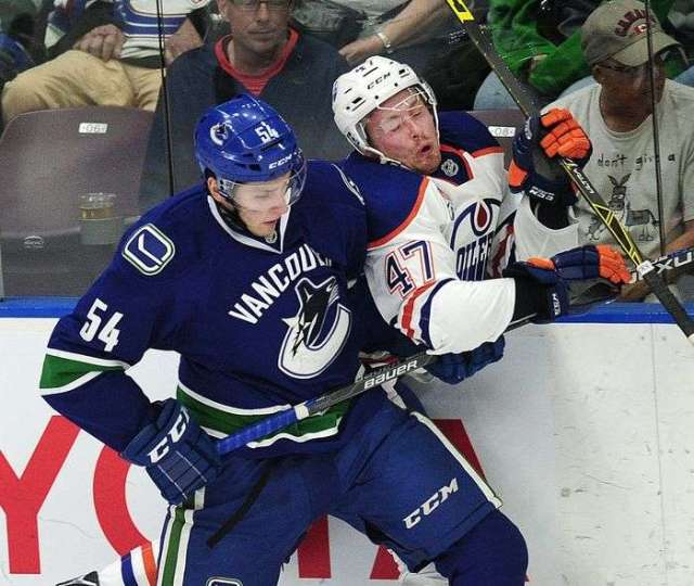 Vancouver Canucks' Guilaume Brisebois (54) against the boards with Edmonton Oilers' Joey Benik (47) during second period 2016 NHL Young Stars Classic action at the South Okanagan Events Centre in Penticton, BC., September 16, 2016.