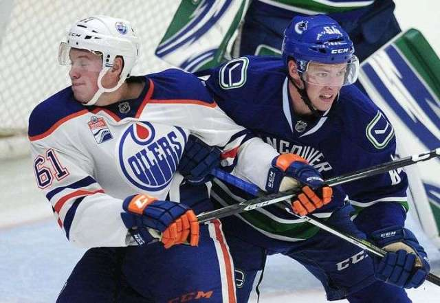 Vancouver Canucks' Tate Olsen (64) in front of the goal with Edmonton Oilers' Braden Christoffer (61) during second period 2016 NHL Young Stars Classic action at the South Okanagan Events Centre in Penticton, BC., September 16, 2016.