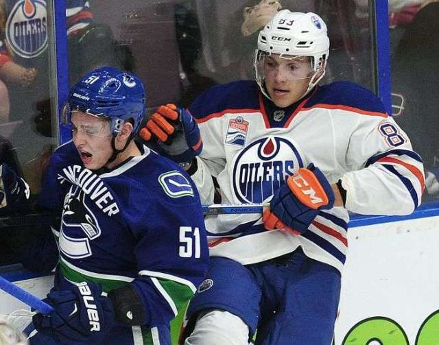 Vancouver Canucks' Troy Stecher (51) against the boards with Edmonton Oilers' Matt Benning (83) during second period 2016 NHL Young Stars Classic action at the South Okanagan Events Centre in Penticton, BC., September 16, 2016.
