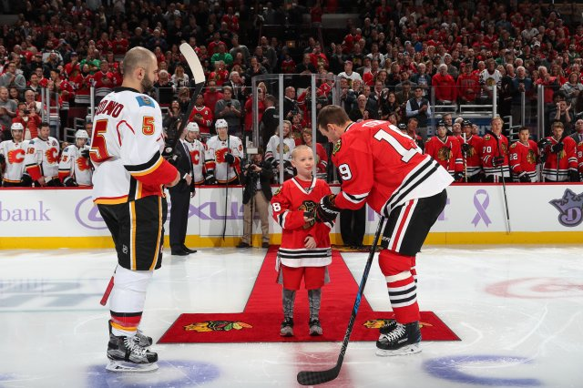 CHICAGO, IL - OCTOBER 24:  Brandon Otte participates in the ceremonial puck drop with captians Mark Giordano #5 of the Calgary Flames and Jonathan Toews #19 of the Chicago Blackhawks  during Hockey Fights Cancer awareness night at the United Center on October 24, 2016 in Chicago, Illinois.  (Photo by Chase Agnello-Dean/NHLI via Getty Images)