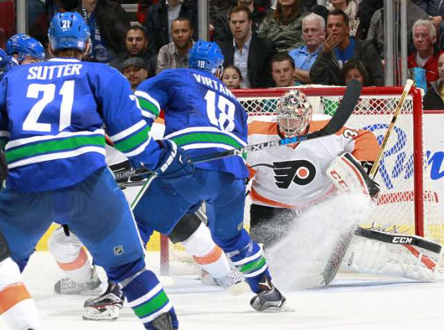 VANCOUVER, BC - NOVEMBER 2: Brandon Sutter #21 watches as Jake Virtanen #18 of the Vancouver Canucks scores his first NHL goal against Steve Mason #35 of the Philadelphia Flyers during their NHL game at Rogers Arena November 2, 2015 in Vancouver, British Columbia, Canada. Vancouver won 4-1. (Photo by Jeff Vinnick/NHLI via Getty Images)