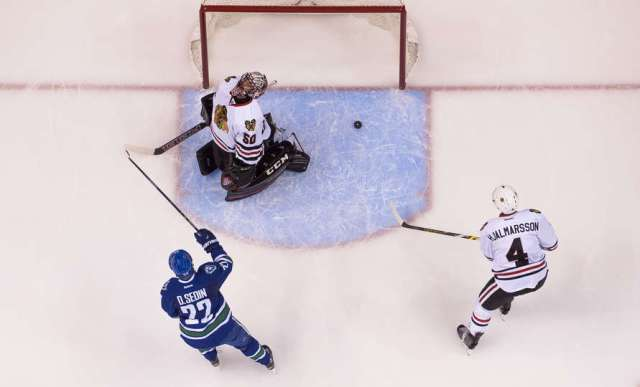 VANCOUVER, BC - NOVEMBER 21: Daniel Sedin #22 of the Vancouver Canucks celebrates after scoring on goalie Corey Crawford #50 of the Chicago Blackhawks as Niklas Hjalmarsson #4 skates past in NHL action on November, 21, 2015 at Rogers Arena in Vancouver, British Columbia, Canada. (Photo by Rich Lam/Getty Images)