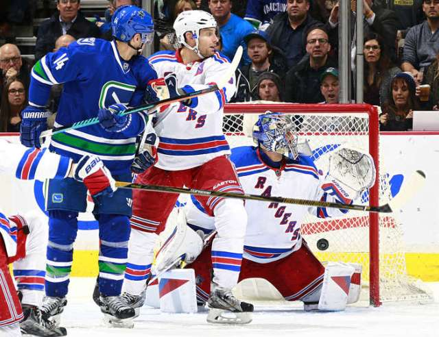 VANCOUVER, BC - DECEMBER 9: Alexandre Burrows #14 of the Vancouver Canucks and Dan Girardi #5 of the New York Rangers watch a shot by Alexander Edler #23 of the Vancouver Canucks beat Henrik Lundqvist #30 of the New York Rangers during their NHL game at Rogers Arena December 9, 2015 in Vancouver, British Columbia, Canada. Vancouver won 2-1. (Photo by Jeff Vinnick/NHLI via Getty Images)