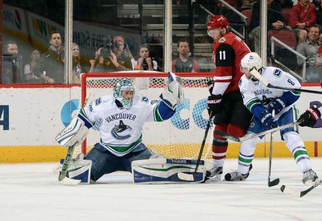 GLENDALE, AZ - FEBRUARY 10: Goalie Ryan Miller #30 of the Vancouver Canucks makes a glove save in front of teammate Christopher Tanev #8 and Martin Hanzal #11 of the Arizona Coyotes during the third period at Gila River Arena on February 10, 2016 in Glendale, Arizona. (Photo by Norm Hall/NHLI via Getty Images)