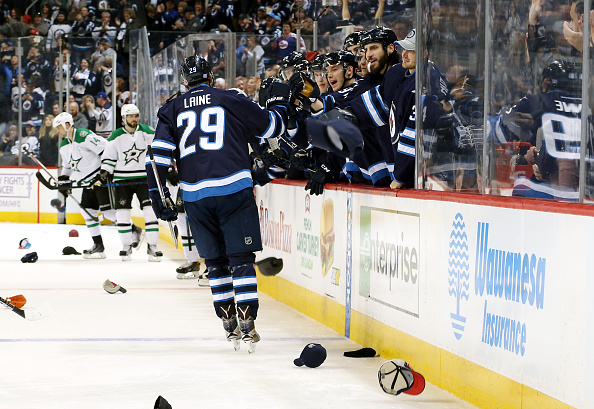 WINNIPEG, MB - NOVEMBER 8: Patrik Laine #29 of the Winnipeg Jets celebrates his third goal of the night against the Dallas Stars with teammates at the bench while hats rain down on the ice at the MTS Centre on November 8, 2016 in Winnipeg, Manitoba, Canada. (Photo by Jonathan Kozub/NHLI via Getty Images)