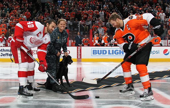 "PHILADELPHIA, PA - NOVEMBER 08: US NAVY Petty Officer 2nd Class Ashlea Scully and her Military Working dog ""OJ"" participate in a ceremonial opening faceoff during Military Appreciation Night with Claude Giroux #28 of the Philadelphia Flyers and Henrik Zetterberg #40 of the Detroit Red Wings on November 8, 2016 at the Wells Fargo Center in Philadelphia, Pennsylvania.  (Photo by Len Redkoles/NHLI via Getty Images)"