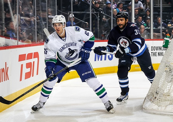WINNIPEG, MB - NOVEMBER 18: Alexandre Grenier #65 of the Vancouver Canucks and Dustin Byfuglien #33 of the Winnipeg Jets follow the play around the net during first period action at the MTS Centre on November 18, 2015 in Winnipeg, Manitoba, Canada. The Jets defeated the Canucks 4-1. (Photo by Jonathan Kozub/NHLI via Getty Images)