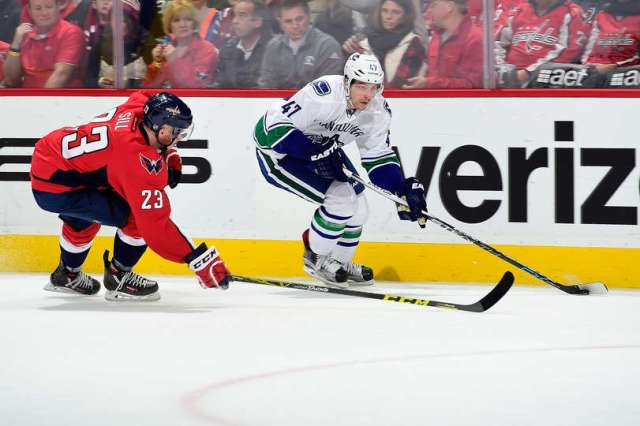WASHINGTON, DC - JANUARY 14: Sven Baertschi #47 of the Vancouver Canucks skates with the puck past Zach Sill #23 of the Washington Capitals in the second period during a game at Verizon Center on January 14, 2016 in Washington, DC. (Photo by Patrick McDermott/NHLI via Getty Images)