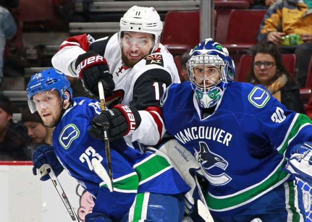 VANCOUVER, BC - JANUARY 4: Martin Hanzal #11 of the Arizona Coyotes reaches for the puck over Alexander Edler #23 of the Vancouver Canucks and Ryan Miller #30 during their NHL game at Rogers Arena January 4, 2017 in Vancouver, British Columbia, Canada. (Photo by Jeff Vinnick/NHLI via Getty Images)