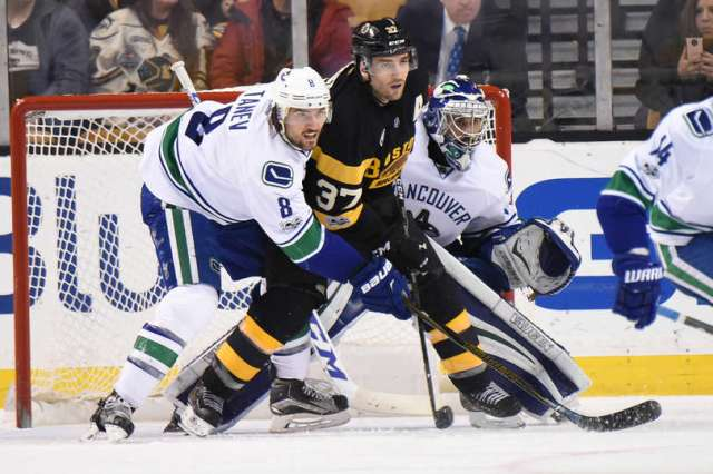 BOSTON, MA - FEBRUARY 11: Patrice Bergeron #37 of the Boston Bruins watches the play against Christopher Tanev #8 and Ryan Miller #30 of the Vancouver Canucks at the TD Garden on February 11, 2017 in Boston, Massachusetts. (Photo by Brian Babineau/NHLI via Getty Images)